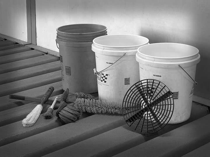 Photograph of various car wash tools including three 5 gallon buckets, wheel and spoke brushes, horse hair brushes, and a grit guard.