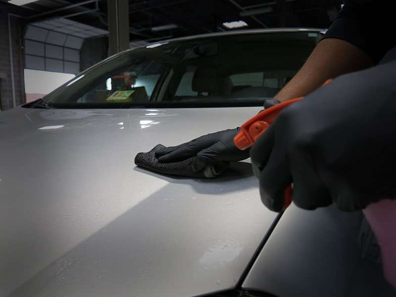 A photograph showing proper use of a clay bar towel that is lubricated by a quick detail spray