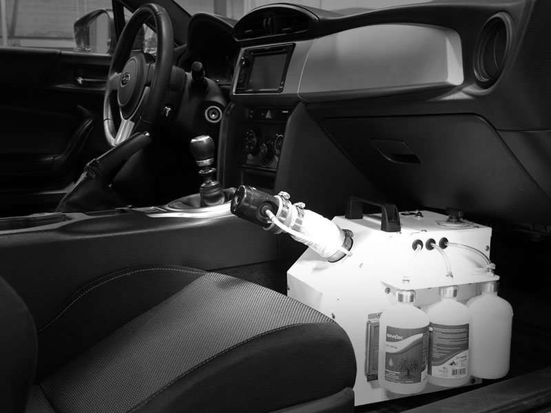 A photograph of the DrivePur PurBlast fogger deodorizing and disinfecting the interoro of a car