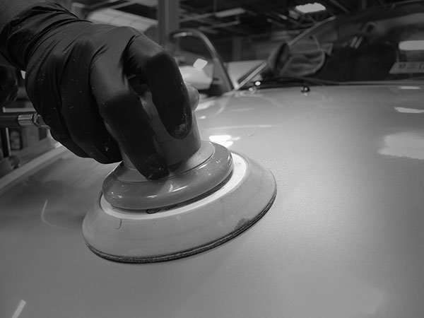 photograph of a car hood undergoing paint correction wet sanding