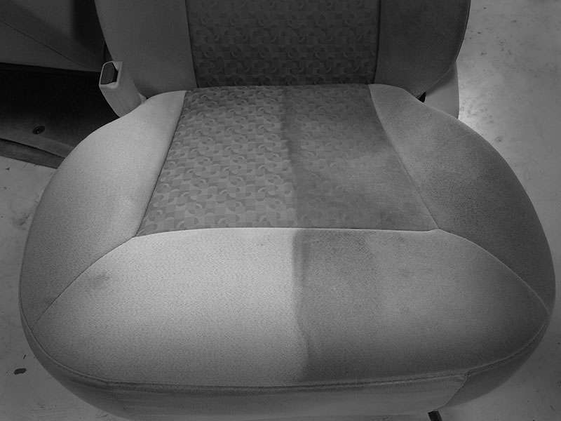 A photograph of a car seat where half has been cleaned with deep hot water extraction - a noticeable difference between two sides of the seat - at Automotive Quality Solutions